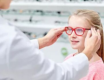 optician putting glasses on a child
